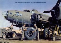 B-17 bomber mechanics changing a main landing gear tire. Note the number two engine undergoing service.