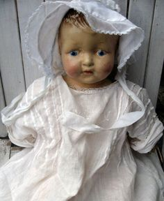 Old doll in vintage baby clothes