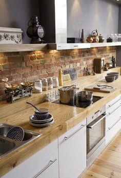 Great mixture of textures from a brick backsplash to white cabinets to a light wood countertop.