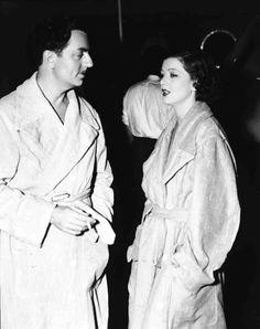 Medium BTS shot of William Powell as Bill Chandler, holding cigarette, and Myrna Loy as Connie Allenbury, wearing bathrobes.