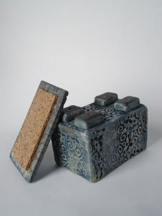 This Asian style box has a cork lined lid that sit securely in place. The perfect box to hold your keepsakes. measures 3.5 x 2.5 x 3 Raku is a alternative firing technique where clay pieces are pulled from the kiln while glowing red hot (about 1800◦F). They are placed in a metal container of combustible materials that ignite on contact and are covered to smoke. This method of firing brings out rich lusters, flashes of color, and intricate crackle patterns to create a unique, one of a ki...
