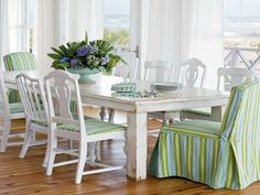 Mismatched chairs unified by white paint and fabric, rustic table