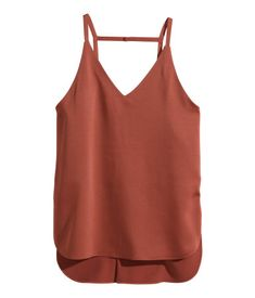 Camisole top in woven fabric with a slight sheen. Deep V-neck at back, narrow shoulder straps, and rounded hem with slits at sides. Slightly longer back section. Lined at top.