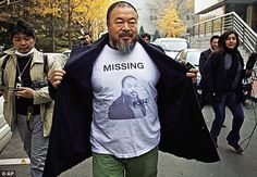 The dissident artist Ai Weiwei reveals a shirt bearing his portrait as he walks into the Beijing Local Taxation Bureau. Ai is forbidden from travelling, is under 24-hour surveillance and lives in constant fear of re-arrest