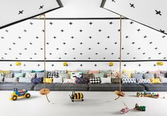 Black and white attic playroom features a white ceiling and wall clad in Urban Walls Plus Signs ...