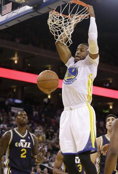 Golden State Warriors small forward Andre Iguodala (9) dunks over Utah Jazz power forward Marvin Williams (2) and others during the second quarter of an NBA basketball game in Oakland, Calif., Saturday, Nov. 16, 2013. (AP Photo/Jeff Chiu)