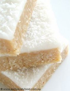 Lemon Coconut Slice Recipe ~ This quick and easy no-bake slice has a moist, coconutty base and a soft, sweet lemon icing. It is finished with a sprinkling of coconut. Milk Recipes, Sweet Recipes, Cookie Recipes, Dessert Recipes, Yummy Recipes, Mexican Recipes, Just Desserts, Delicious Desserts, Yummy Food