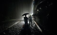 Rescue workers stand in the rain near the coaches of the derailed Vidarbha Express train near Kasara, about 100km (62 miles) from Mumbai