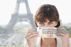 Woman showing 50 Euro banknote with the Eiffel Tower in the background, Paris, Ile-de-France, France