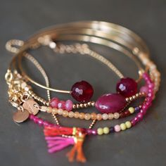Why not put beads on a wire with charms and tassel interspersed and put on interchangeable bangles = could be fun colors and low cost!