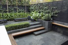 Contemporary garden with clean lines. Love the dark stone.