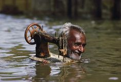 Man with sewing machine in a river...