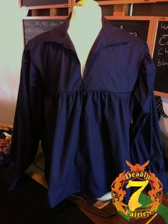 This is a Men's Navy Peasant Shirt. It is a perfect item for a Men's Renaissance Faire outfit. It is made of 100% cotton. It has a open front, collar, and cuffs which can be turned up. It is available in sizes Small through XLarge. It has a fitted chest cut, with a pleated torso on the front and black, to allow for a wide range of motion and movement and gives a billowed effect when belted or tucked in.