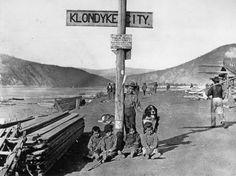 1890: Children of the Klondike area of Yukon Territory, Canada, sitting with their dog by a street sign.