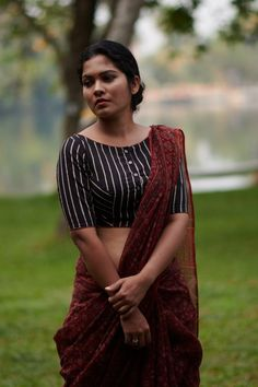 This red pinstriped shirt blouse has a bias waist band that gives it an old world charm. Hand-block printing detail adds to the quaint look. THE KAITHARI PROJECT Handwoven and designed in Kerala Kalamkari Blouse Designs, Cotton Saree Blouse Designs, Fancy Blouse Designs, Dress Neck Designs, Stylish Blouse Design, Bollywood, Designer Blouse Patterns, Ethnic, Kerala
