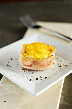 Using a muffin/cupcake pan, line the holes with a slice of bacon, pressing the bacon around the sides of the hole, not on the bottom. Crack one egg into each hole. Sprinkle with salt, cracked black pepper and cheese.  Bake at 350 degrees for 20 minutes or longer for crispier bacon. Pop out of the muffin tins and serve.