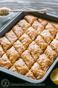 Homemade baklava displayed sliced in baking sheet drizzled with hot honey lemon syrup for the best baklava recipe