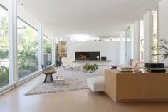 The beauty of the A. Quincy Jones design: The 11-foot-high ceiling angles gracefully down toward a white brick fireplace, which anchors a more intimate end of the room. Sliding glass opens to a courtyard and pool on one side, to a steep driveway that disappears from sight on the other. A white sofa effortlessly sweeps along the wall, adding to the visual harmony.