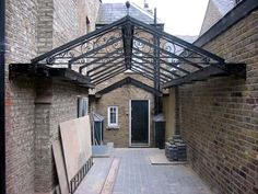 Photographed when partially completed, this canopy creates a covered courtyard. The canopy was designed so that the gutters either side act as walkways, to allow cleaning and servicing of the glass roof. A cat ladder was included