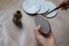 Apply two coats of gold paint around the coaster edges and let dry for at least 20 minutes. | We Made Fancy-Looking Faux Marble Coasters For Under $20