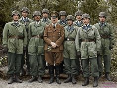 """Chancellor Adolf Hitler with a group of paratroopers (fallschirmjäger """"green devil"""") decorated with the Iron Cross for having breached the Belgian fort of Eben Emael, Belgium May 1940."""