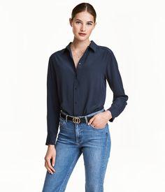 Mørk blå. PREMIUM QUALITY. En bluse i crêpet muldbærsilke. Blusen har krage og knapping foran. Avrundet kant nederst.