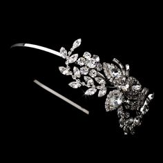 "Elegant and modern, this wedding piece will dazzle on your special day. An artistic and abstract floral arrangement of clear rhinestones sits to one side of the silver-plated band. A perfect accessory for your white or ivory wedding dress, this headband is a unique statement of loveliness.  14"" in length; detailing measures 5"" in length and"