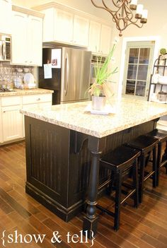 #kitchen island redo - different colour than main cabinetry. While I like the black, I don't like the rustic look. I do love the support columns, this would stop the kids from running under the counter and baging their heads. I also like the framing and moulding along the base. This couls work for us.