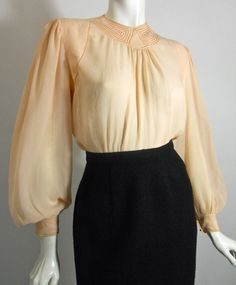 Pale peach silk 1930s blouse with deco topstitch and cutwork design at neckline, openwork down to side seams. Billowing sleeves full at cuff. Buttons up back with mother of pearl buttons, from Bullocks Wilshire.