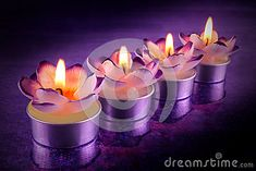 Burning flower shaped candles lined up on purple reflective surface.