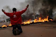 Membro do MTST se ajoelha diante de barricada em chamas em manifestação nesta manhã de sexta (28) em Brasília  (Foto: Ueslei Marcelino/Reuters)