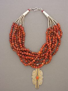 by Anne Holland | An old silver and carnelian Tekke Turkoman pendant with seven strands  of old carnelian beads from Mali, silver heishi, sterling silver cones, and  a sterling silver hook and eye clasp that was handmade in Sri Lanka | Sold