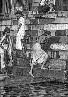 Mother Ganges Monochrome.  Women greet the morning sun with a purifying bath in the the holy Ganges at Varanasi, India. Hindu pilgrims hope to achieve moksha, an end to the cycle of death and rebirth, by washing away their sins in the sacred waters. This scene has played out on these steps for thousands of years.