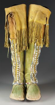 A pair of Comanche beaded hide hightop moccasins. c. 1880... each painted overall in green and yellow pigments, decorated on the leg with narrow bands of geometric beadwork, stitched with sinew in various shades of small glass seed beads, trimmed with two rows of brass tacks and twisted hide fringe, rawhide soles.
