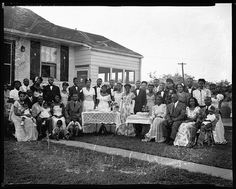 Posed group of African American men, women and children in formal attire in front of a house.  Vintage African American photography courtesy of Black History Album, The Way We Were.  Follow Us On Twitter @blackhistoryalb