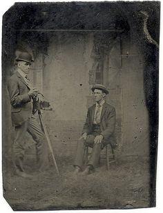 Tintype of Folding Camera on Tripod    The clumsily hung backdrop says interior but the real looking grass under the two young men says outdoor.