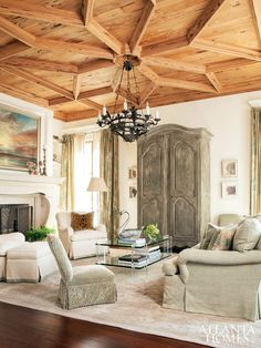 beautiful grand coastal living room features an amazing ceiling with detailed wood work. the proportion of the over-sized rustic french armoire in a grey wash against all the natural wood adds interest in a large space. architectural design firm Spitzmiller & Norris, Rosemary Beach, FL