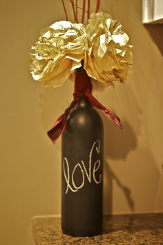 looks like you pain old wine bottles with chalkboard paint? Wrap ribbon/fabric of your choice and fill with flowers of your choice...