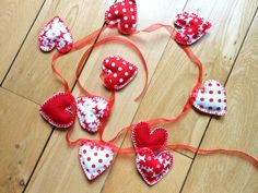 This bunting is made from 10 heart shapes, cut out and sewn by hand. They are stuffed with toy stuffing and are made from red and white material of various patterns. Each heart is finished with blanket stitch in embroidery thread and then hand sewn onto red organza ribbon for hanging.    The total length of the bunting is just under 1.8m, this includes a good length at each end to allow for hanging. Each padded heart is around 6.5cm long and 6cm wide