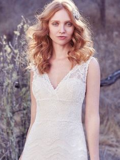 Maggie Sottero - BRYNN, Chic and boho-inspired, this sheath wedding gown features horizontal lace motifs. Sheer lace and side insets comprise the gown's straps, completing the V-neckline and square back. Finished with covered buttons over zipper closure.