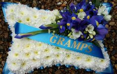Cushion tribute with name banner and spray, edged with pleated ribbon.