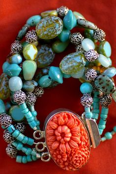 Turquoise beads with carved coral clasp as accent.