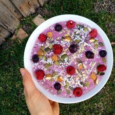 Smoothie bowl made with frozen banana, mixed berries, almond milk and chia seeds and topped with raspberries, blueberries, raw almonds, pepitas, sunflower seeds, chia seeds and shredded coconut