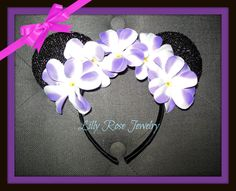 You are purchasing a lightweight pair of black Sparkly Minnie Mouse ears Inspired headband with white and purple plumeria flowers. Great for adults or kids. Sparkly fabric is only in front back is plain black. This is already made and ready to ship. I am only shipping within the United States at this time.  Disclaimer: This is not a licensed Disney product. I am not affiliated with or sponsored by Disney Enterprises. I do not claim to own copyright. These are simply inspired and handcrafted…