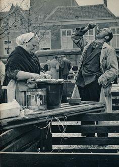 Kees van Wijk- Den Haag scheveningse visverkoopster 1957 - Fresh Herring at the dock.  www.parfumflowercompany.com