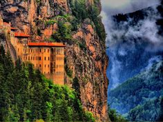 """The Sümela Monastery, is a Greek Orthodox monastery dedicated to the Virgin Mary (Panagia, meaning """"All Holy"""" in Greek) at Melá mountain, in the region of Maçka in the Trabzon Province of modern Turkey. Nestled in a steep cliff at an altitude of about 1,200 metres (3,900 ft) facing the Altındere valley, it is a site of great historical and cultural significance, as well as a major tourist attraction of Altındere National Park."""