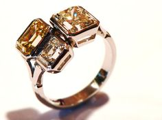 This stunning cocktail ring has three emerald-cut diamonds of different sizes and colours, all in hand made platinum rub-over settings. One stone is blue-white, one yellow and one light cognac colour. Rings can be designed to accommodate any shape, type and colour of gemstone.