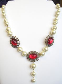 """An elegant set consisting of a 19"""" necklace featuring large, 12 mm glass pearls in a warm ivory tone, and three ruby red glass jewels glowing in their filigree settings. Matching earrings measure 3/4"""" from their French hook surgical steel ear wires. Who doesn't look good in big pearls?! $40"""