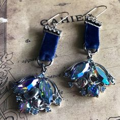 Repurposed vintage blue aurora borealis crystal earrings are suspended from strips of deep blue velvet and sterling silver rings. Vintage rhinestones accent these one of a kind handmade earrings. Earring length is approx. 2 1/2 not including the sterling silver earring wires.