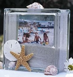 Glass block with sand and picture frame inside.